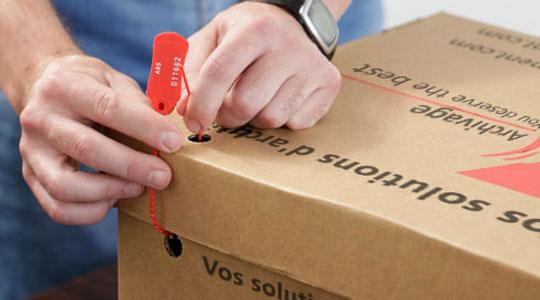Mains sécurisant une boîte d'archives / Hands securing records archive